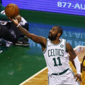Kyrie Irving nostaa yhdellä kädellä palloa koriin.