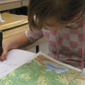 Koululainen maantiedonkirjan äärellä