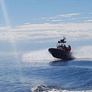 sjöräddningsbåt kör i full fart på solblänkande hav
