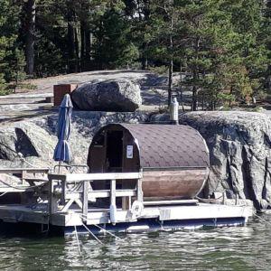 En bastu på en brygga utanför klippor vid en holme.