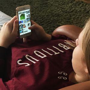 Tyttö löhöää nojatuolissa ja selaa kännykällä Instagramia