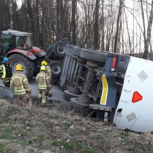 En traktor med släpvagn på vägen. Släpvagnen har vält. Räddningsmanskap på plats.