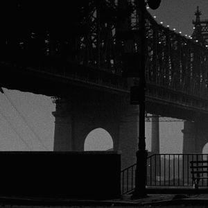 Isaac ja Mary (Woody Allen ja Diane Keaton) istuvat puistonpenkillä selin kameraan katsellen valaistua siltaa. Kuva elokuvasta Manhattan