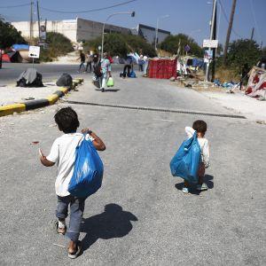 Kaksi lasta kävelee pakolaisleirissä Kreikassa.