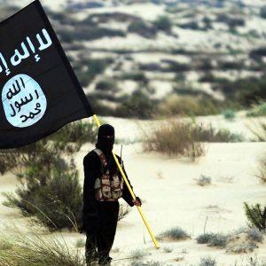 Ihminen pitelee terroristijärjestö Isisin lippua.