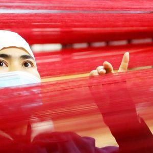 Mattoja valmistavan tuontantolaitoksen työntekijä Ürümqin kaupungissa Xinjiangissa marraskuussa 2020.