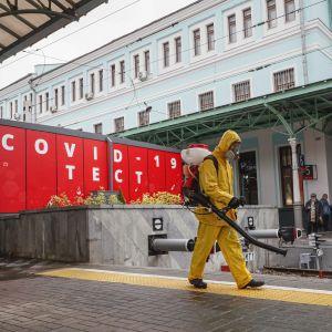Työntekijä puhdistaa suojapuvussa juna-asemalla sijaitsevaa korona-testipaikan edustaa.
