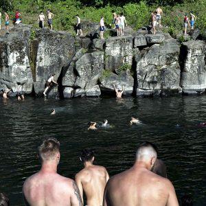 Uimarit hyppivät rantakalliolta jokeen.