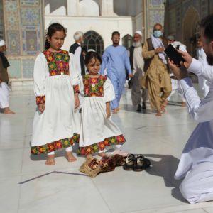 Afgaanitytöt poseerasivat isälleen uusissa mekoissa tiistaina länsiafganistanilaisen Heratin moskeijan edessä.