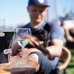 Mies koira sylissä ravintolan terassilla Helsingissä.