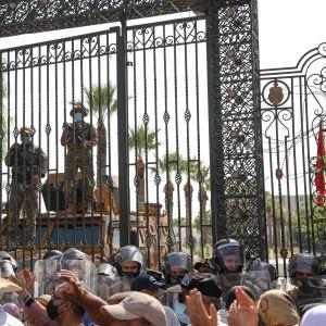 Väkijoukko ja mellakkapoliiseja suljetun portin edessä, portin takana asemiehiä.