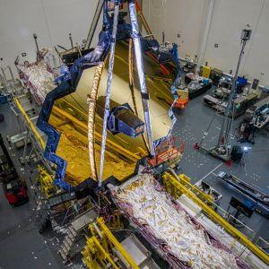 Laitteita ja suojapukuihin pukeutuneita tutkijoita hallissa keskeneräisen teleskoopin ympärillä.