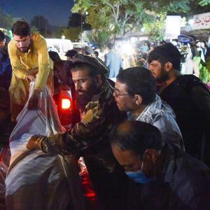 Vapaaehtoiset ja pelastustyöntekijät auttavat iskussa haavoittuneita.