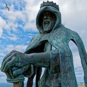 Viittaan kietoutunutta, miekkaa pitelevää kruunupäistä miestä esittävä patsas sinitaivasta vasten.