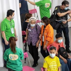 Ihmisiä rokotuskesksuksessa Hongkongissa.