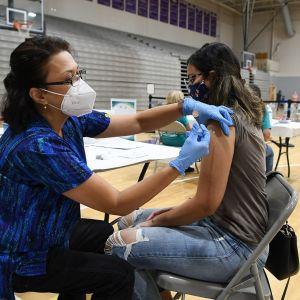 Kuvassa hoitaja rokottaa naisasiakasta.
