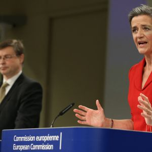 Margrethe Vestager tiedotustilaisuudessa, taustalla näkyy Dombrovskis.