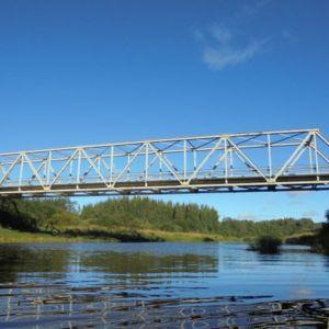 Joen yli kulkeva silta kuvattuna auringonpaisteessa.
