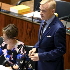 Timo Heinonen seisoo täysistuntosalissa. Hänen vieressän istuu Sari Essayah, joka kirjoittaa jotakin.