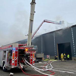 Tulipalo teollisuushallissa Kauhavalla. Kalustoa ja pelastuslaitoksen miehistöä paikalla.