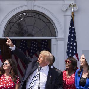 Trump on kuvassa lehdistötilaisuudessa. Hän osoittaa oikealla kädellään kohti taivasta.