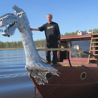 Mies seisoo veneen kannella.