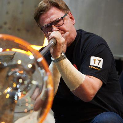 Mies puhaltaa lasivatia lasinpuhalluskilpailuissa