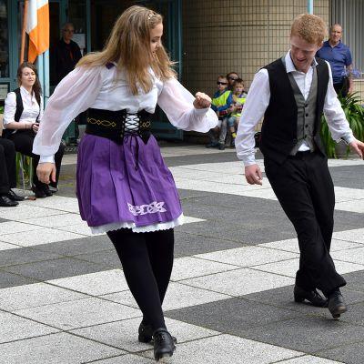 Irlantilaisen kansantanssiryhmän kaksi jäsentä esiintyy kirjaston pihassa, taustalla soittajia