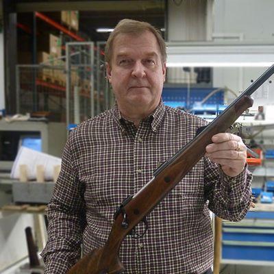 Mies esittelee kivääriä.