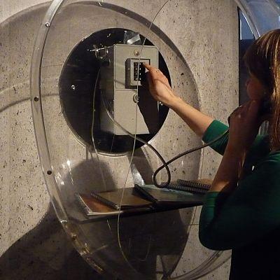 Nainen valitsee numeroa yleisöpuhelimessa Tampereen Rupriikki-museossa