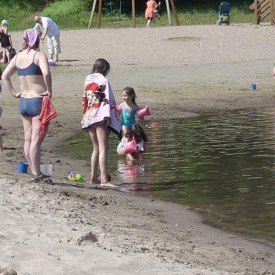 Väkeä kesäisellä uimarannalla.