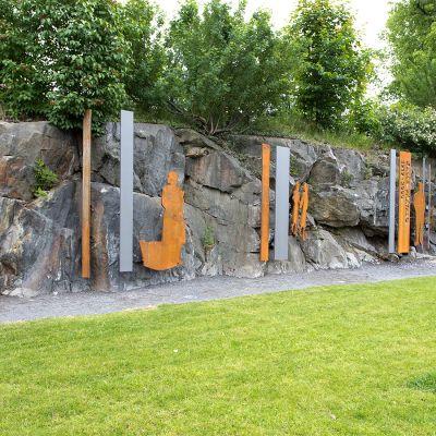 Kalle Päätalon muiston kunniaksi tehty veistos luonnonkallio-ja betoniseinässä