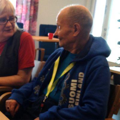 Vanhempi mies ja nainen istuvat pöydän ääressä