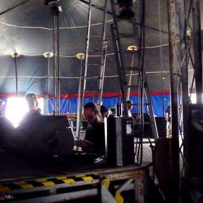 Esiintymislava teltan sisällä, miehiä kasaamassa kaiuttimia ja valoja lavalle.