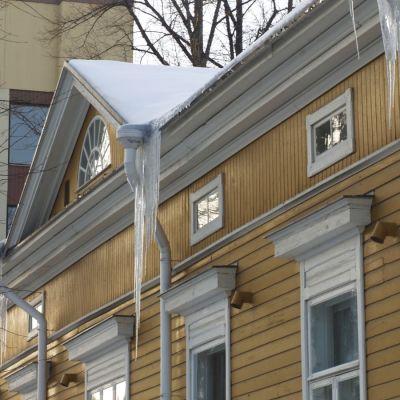Jääpuikkoja roikkuu puutalon räystäästä.