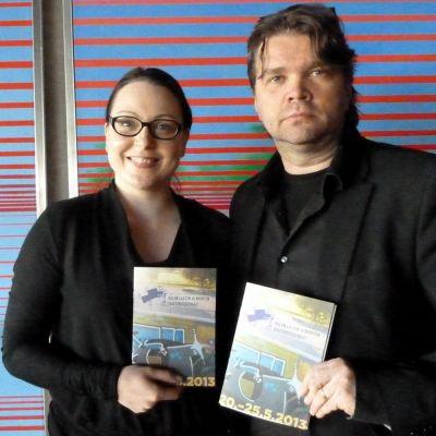 Sari Tanner ja Mikko Kouki poseeraavat kädessään Lasten ja nuorten teattarifestivaalin ohjelmalehtiset