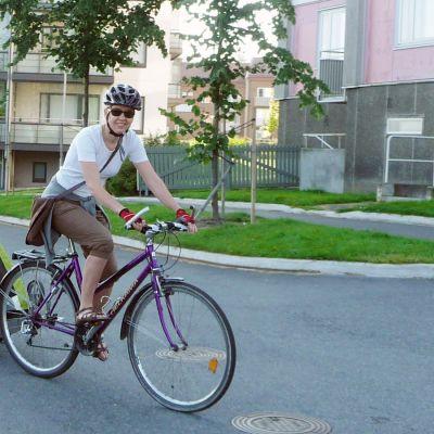 Nainen polkee pyörää, jonka perävaunussa on lapsi