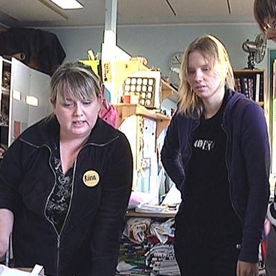 Nainen neuvoo kahta tyttöä ompelutyössä.