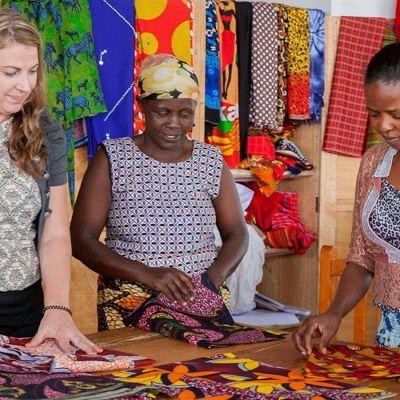 Katja Kokkoniemi ja kaksi namibialaisnaista afrikkalaisten kankaiden äärellä