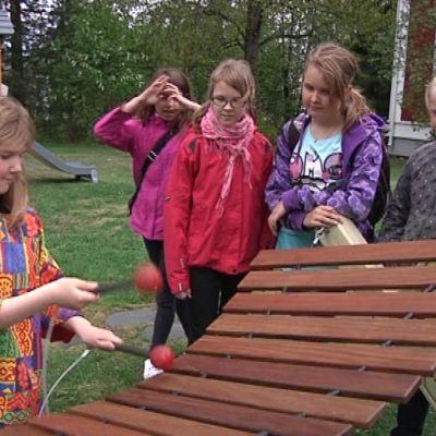 lapset soittavat suurta puistosoitinta