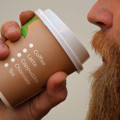 Mies juo kahvia kertakäyttökupista