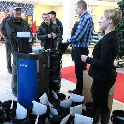 Radonmittauspurkkeja muoviämpärin kera jaettiin kauppakeskuksessa.