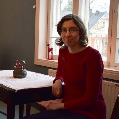 Nainen istuu pöydän ääressä joulukahvilassa