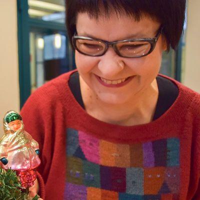 Taja Filatov katsoo naista kuvaavaa joulukoristetta kuusenoksalla