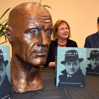 Sakari Pälsistä kertovan kirjan toimittajat poseeraavat kirjojen ja Pälsin rintakuvan kanssa