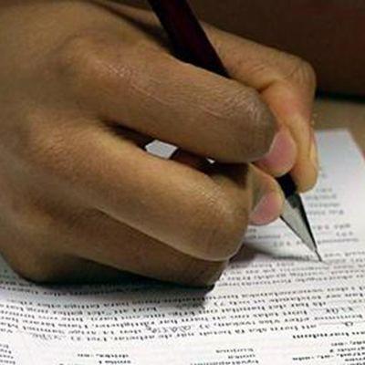 En hand som skriver på ett papper.
