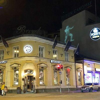 Ljuskonst med en stående man på Turun Sanomats byggnad på Köpmansgatan i Åbo.