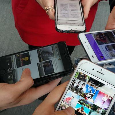 Fyra unga som håller sina smarttelefoner i förgrunden. Yle Nyhetsskolans logo uppe i vänstra hörnet.