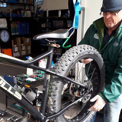 Jörgen Holmström reparerar en cykel. Yle Nyhetsskolans logo i vänstra hörnet.