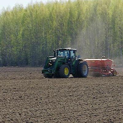 Traktori keväisellä pellolla